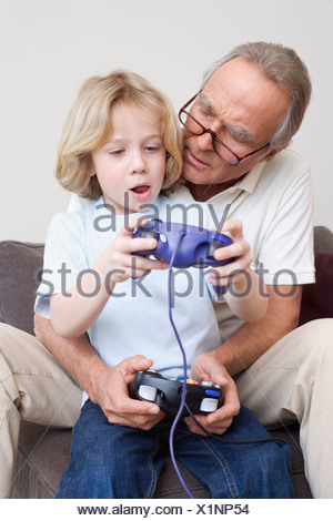 Grandfather and grandson (8-9) playing video game, portrait - Stock Photo
