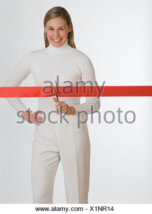 Woman cutting red tape - Stock Photo