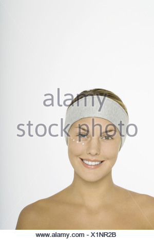 Young woman with dots of moisturizer under eye - Stock Photo