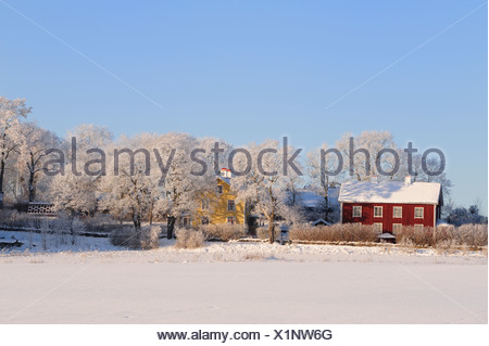 Snow covered landscape with red country houses and frosted trees against clear blue sky - Stock Photo