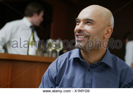 A young man sitting at a table in a hotel bar smiling - Stock Photo