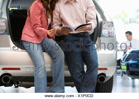 Couple reading brochure in car showroom - Stock Photo
