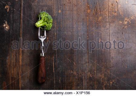 Fresh broccoli on meat fork on dark wooden background - Stock Photo