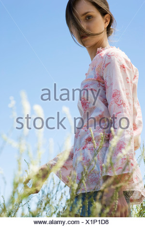 Young woman walking in tall grass, hair tousled by breeze - Stock Photo