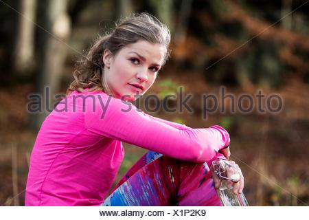 Side view of young woman sitting wearing sports clothes looking at camera - Stock Photo