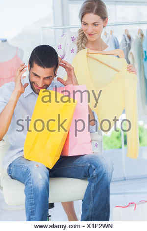 Angry man while his girlfriend is shopping - Stock Photo