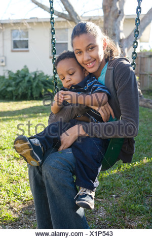 African American pre-teen girl sitting on swing holding baby brother in backyard - Stock Photo