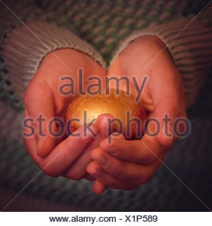 A girl holding golden nest egg in her hands - Stock Photo