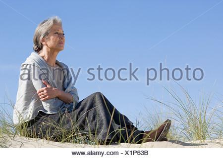Senior woman relaxing on a beach - Stock Photo