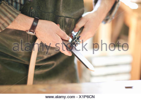 Male worker in leather workshop, punching holes in leather belt, mid section, close-up - Stock Photo