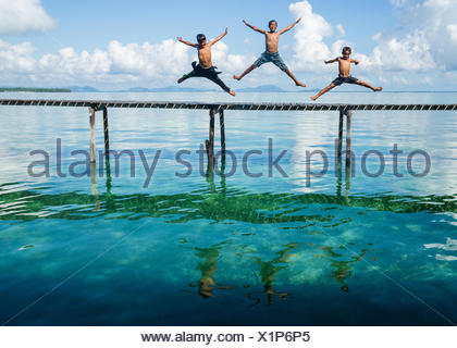 Three boys jumping in to the sea from a jetty, Salakan Island, Semporna, Sabah, Malaysia - Stock Photo