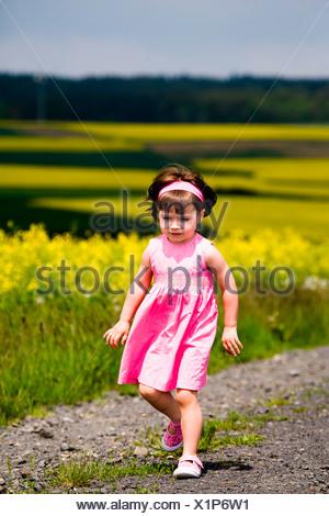 Little girl walking on field path - Stock Photo