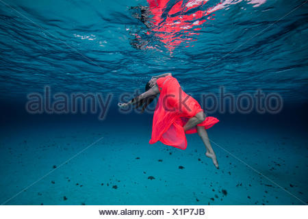 Woman underwater in red dress - Stock Photo
