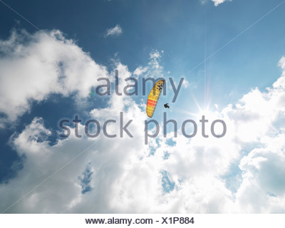 Senior paraglider in midair against sky - Stock Photo