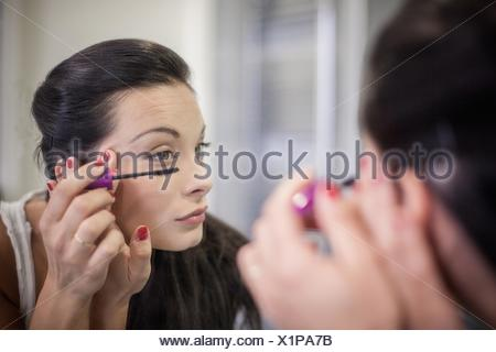 Over the shoulder mirror image of young woman applying mascara - Stock Photo