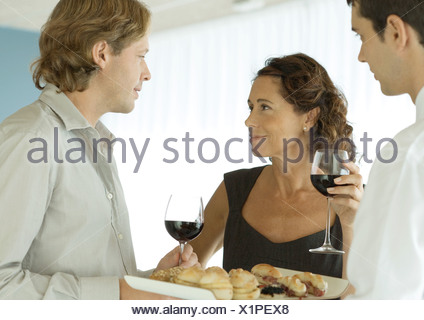 Woman smiling at man in cocktail party - Stock Photo