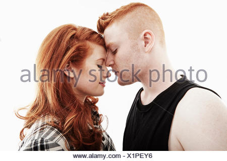 Studio portrait of red haired young couple head to head with eyes closed - Stock Photo