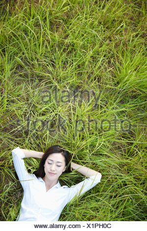 a woman lying on the grass - Stock Photo