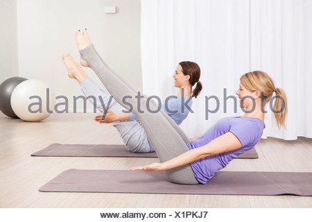 Two women doing Pilates exercise, feet outstretched - Stock Photo