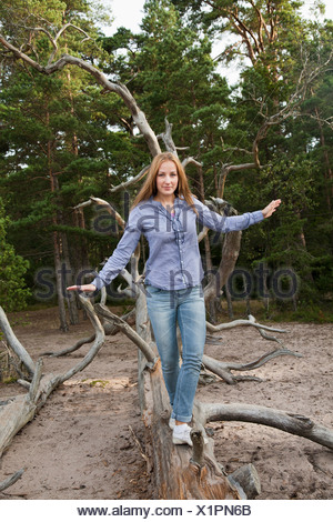 Woman balancing on fallen tree - Stock Photo