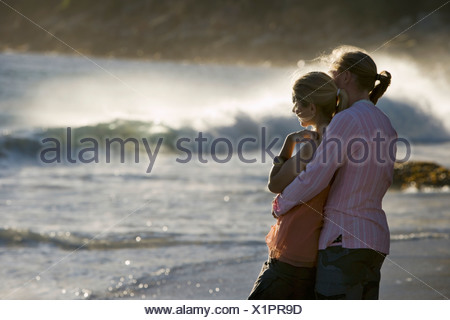 Affectionate teenage couple 17 19 standing on beach near surf boy embracing girl side view - Stock Photo