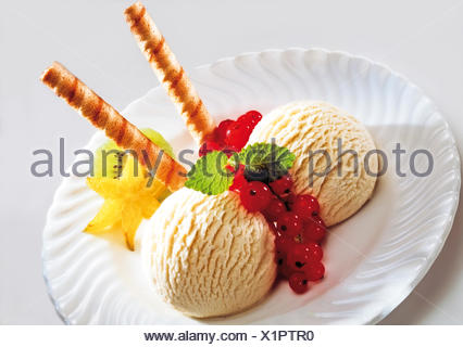 Two scoops of vanilla ice cream with fruit and wafers - Stock Photo