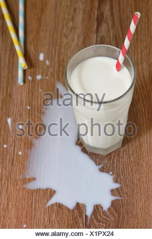 Milk spilled from glass on wooden table. - Stock Photo