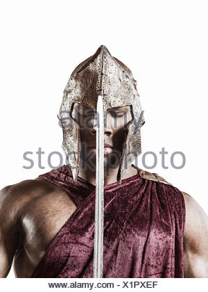 Studio portrait of poised young man dressed as gladiator with helmet and sword - Stock Photo
