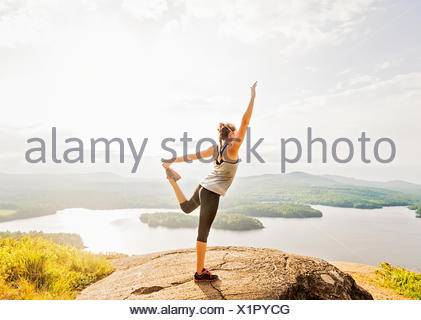 Side view of young woman exercising on mountain top - Stock Photo