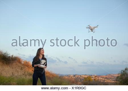 Female commercial operator flying drone looking up smiling, Santa Clarita, California, USA - Stock Photo