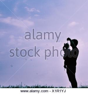 Silhouette of man and child blowing bubbles - Stock Photo