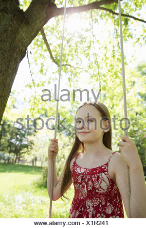 Summer. A girl in a sundress on a swing in an orchard. - Stock Photo
