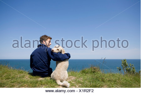 A man with his arm around a dog sitting by the sea - Stock Photo