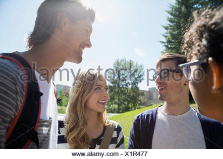 College students talking in circle on sunny campus - Stock Photo
