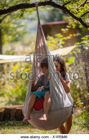 Girl pushing a boy on a swing in the garden - Stock Photo