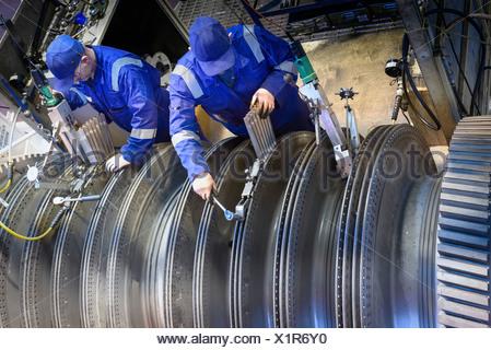 Engineers fitting blades to steam turbine in turbine repair bay - Stock Photo