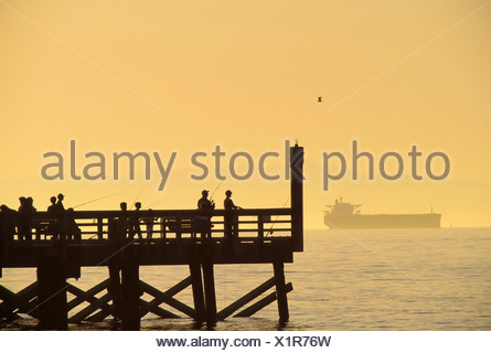 People fishing off dock by Burrard Inlet with freighter in the background, West Vancouver, British Columbia, Canada - Stock Photo