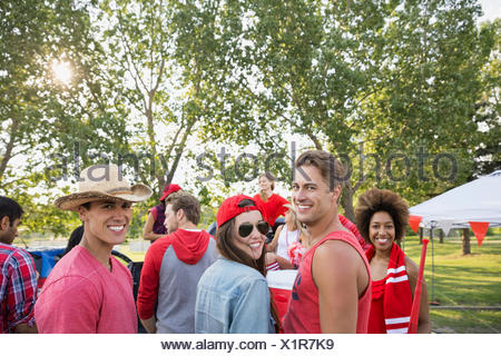 Friends relaxing together at barbecue in field - Stock Photo