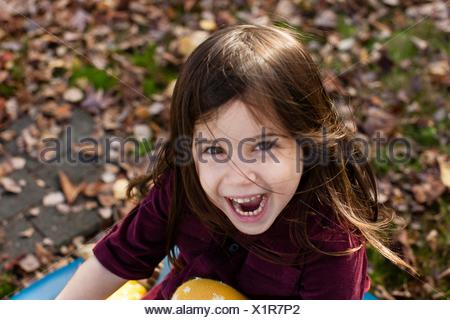 High angle portrait of young girl among autumn leaves looking at camera open mouthed smiling - Stock Photo
