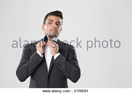 Man in tuxedo adjusting his bow tie - Stock Photo