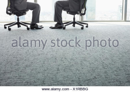 Low section of businessmen sitting on office chairs - Stock Photo