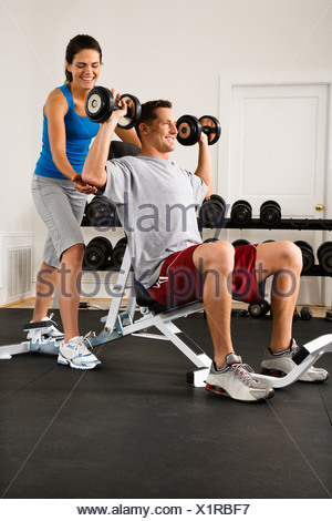 Woman assisting man lifting weights at gym - Stock Photo