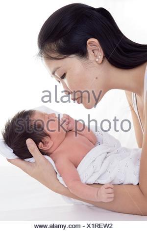MODEL RELEASED. Mother cradling newborn baby girl. - Stock Photo