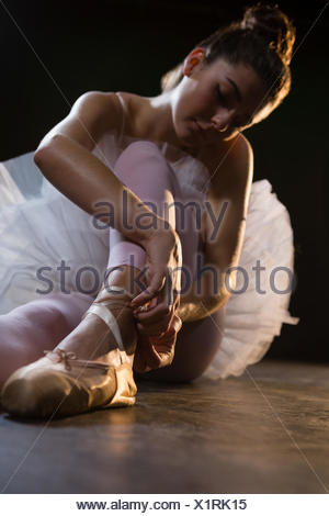 Female ballet dancer tying the ribbon on her ballet shoes in the studio - Stock Photo