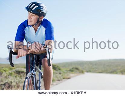 Man in helmet sitting on bicycle - Stock Photo