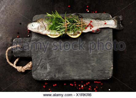 Raw rainbow trout with lemon, herbs and spice on rustic background - Stock Photo