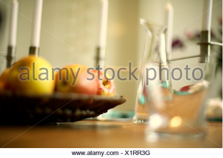 Glasses and fruit bowl on a table - Stock Photo