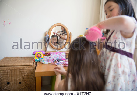 Young girl brushing friends hair in bedroom - Stock Photo