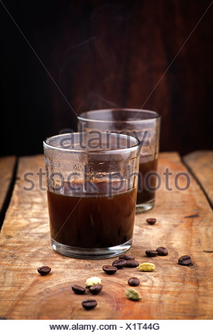 coffee in glass and ingredients on wood background - Stock Photo