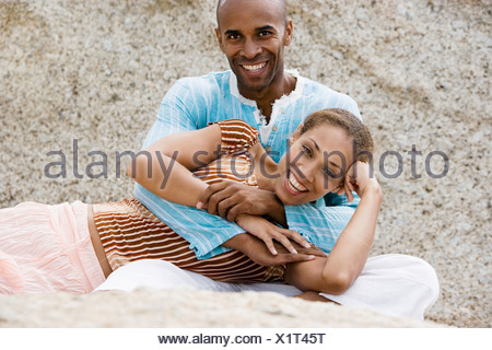 Couple relaxing on rocky beach woman lying in man s lap smiling portrait - Stock Photo
